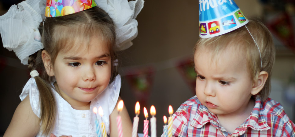 small child blowing out birthday candles