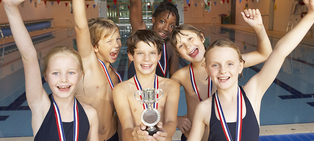 winning swim team with trophy